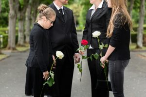Family,Mourning,On,Funeral,At,Cemetery,Standing,In,Group,With